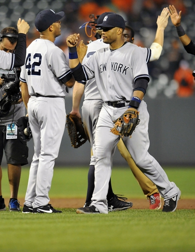 Sep 10, 2013; Baltimore, MD, USA; New York Yankees teammates Marinao Rivera (42) and Robinson Cano (24) celebrate after a game against the Baltimore Orioles at Oriole Park at Camden Yards. The Yankees defeated the Orioles 7-5. Mandatory Credit: Joy R. Absalon-USA TODAY Sports