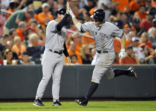Sep 10, 2013; Baltimore, MD, USA; New York Yankees first baseman Mark Reynolds (39) is congratulated by third base coach Rob Thomson (59) after hitting a solo home run in the sixth inning against the Baltimore Orioles at Oriole Park at Camden Yards. The Yankees won 7-5. Mandatory Credit: Joy R. Absalon-USA TODAY Sports