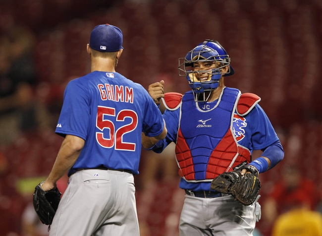 Sep 10, 2013; Cincinnati, OH, USA; Chicago Cubs catcher Welington Castillo (53) congratulates starting pitcher Justin Grimm (52) at the end of the game against the Cincinnati Reds at Great American Ball Park. The Cubs defeated the Reds 9-1. Mandatory Credit: Frank Victores-USA TODAY Sports
