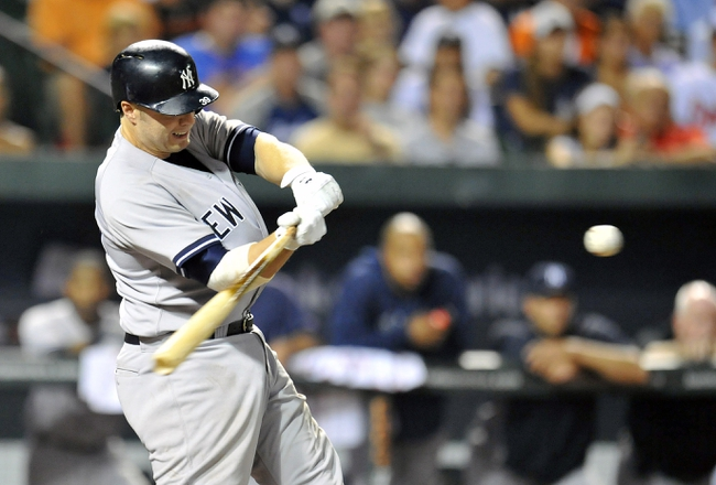 Sep 10, 2013; Baltimore, MD, USA; New York Yankees first baseman Mark Reynolds (39) hits a one-run rbi double in the eighth inning against the Baltimore Orioles at Oriole Park at Camden Yards. The Yankees defeated the Orioles 7-5. Mandatory Credit: Joy R. Absalon-USA TODAY Sports