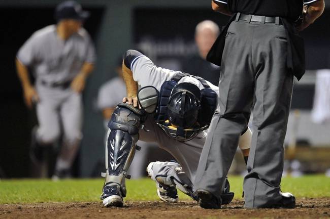 Sep 10, 2013; Baltimore, MD, USA; New York Yankees catcher Austin Romine (53) goes down after taking a foul ball off his helmet in the eighth inning against the Baltimore Orioles at Oriole Park at Camden Yards. The Yankees defeated the Orioles 7-5. Mandatory Credit: Joy R. Absalon-USA TODAY Sports