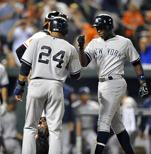 Sep 10, 2013; Baltimore, MD, USA; New York Yankees left fielder Alfonso Soriano (12) is congratulated by Robinson Cano (24) after hitting a two-run go-ahead home run in the eighth inning against the Baltimore Orioles at Oriole Park at Camden Yards. The Yankees defeated the Orioles 7-5. Mandatory Credit: Joy R. Absalon-USA TODAY Sports