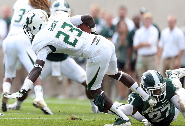 Sep 7, 2013; East Lansing, MI, USA; South Florida Bulls defensive back Kenneth Durden (23) is tripped up by Michigan State Spartans safety Kurtis Drummond (27) while returning a punt during the 2nd half at Spartan Stadium. MSU won 21-6. Mandatory Credit: Mike Carter-USA TODAY Sports