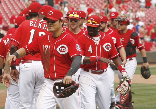 Sep 11, 2013; Cincinnati, OH, USA; Cincinnati Reds center fielder Shin-Soo Choo (17) and second baseman Brandon Phillips (4) are congratulated by teammates after they beat the Chicago Cubs 6-0 at Great American Ball Park. Mandatory Credit: David Kohl-USA TODAY Sports