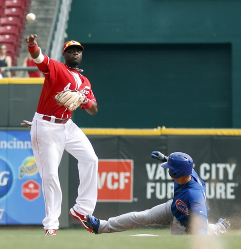 Sep 11, 2013; Cincinnati, OH, USA; Chicago Cubs second baseman Darwin Barney (right) is forced out a second as Cincinnati Reds second baseman Brandon Phillips (4) throws to first to complete a double play in the seventh inning at Great American Ball Park. Mandatory Credit: David Kohl-USA TODAY Sports