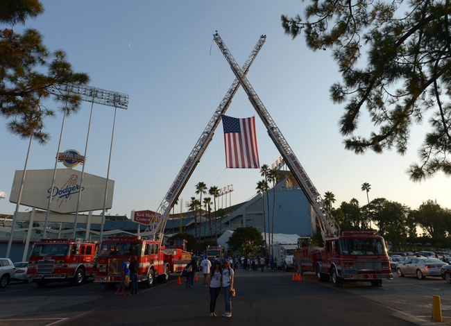 Sep 11, 2013; Los Angeles, CA, USA; City of Los Angeles fire department trucks hoist a United States flag in remembrance of the attacks of September 11, 2001 before the MLB game between the Arizona Diamondbacks and the Los Angeles Dodgers at Dodger Stadium. Mandatory Credit: Kirby Lee-USA TODAY Sports