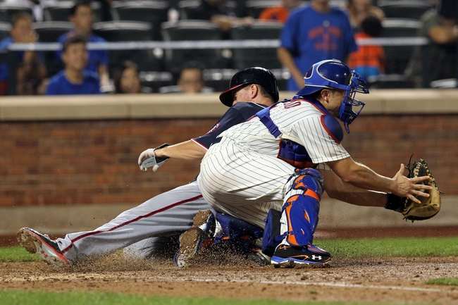 Sep 11, 2013; New York, NY, USA; Washington Nationals first baseman Adam LaRoche (25) slides safely past New York Mets catcher Travis d'Arnaud (15) to score on a double hit by Washington Nationals second baseman Anthony Rendon (not pictured) during the eighth inning of a game at Citi Field. Mandatory Credit: Brad Penner-USA TODAY Sports