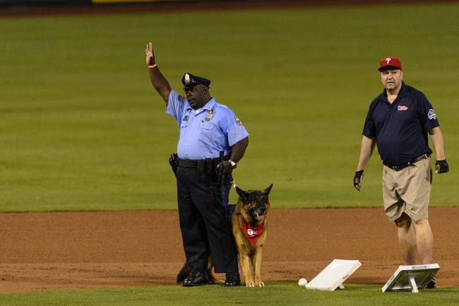 Sep 11, 2013; Philadelphia, PA, USA; Philadelphia police officer Paul Bryant with police dog Deeohgee help change second base during the third inning of a game between the Philadelphia Phillies and the San Diego Padres at Citizens Bank Park. The Phillies defeated the Padres 4-2. Mandatory Credit: Howard Smith-USA TODAY Sports