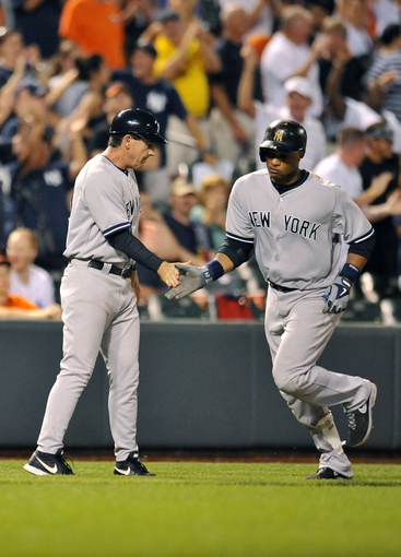 Sep 11, 2013; Baltimore, MD, USA; New York Yankees second baseman Robinson Cano (24) is congratulated by third base coach Rob Thomson (59) after hitting the go-ahead solo home run in the ninth inning against the Baltimore Orioles at Oriole Park at Camden Yards. The Yankees defeated the Orioles 5-4. Mandatory Credit: Joy R. Absalon-USA TODAY Sports