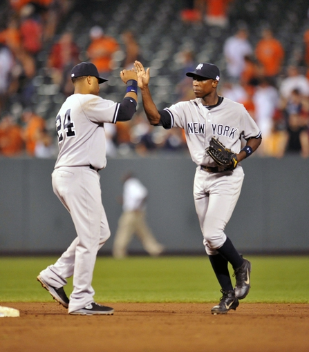 Sep 11, 2013; Baltimore, MD, USA; New York Yankees teammates Robinson Cano (left) and Alfonso Soriano (right) celebrate after a game against the Baltimore Orioles at Oriole Park at Camden Yards. The Yankees defeated the Orioles 5-4. Mandatory Credit: Joy R. Absalon-USA TODAY Sports
