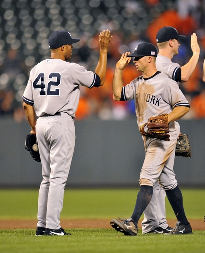 Sep 11, 2013; Baltimore, MD, USA; New York Yankees teammates Mariano Rivera (left) and Brett Gardner (right) celebrate after a game against the Baltimore Orioles at Oriole Park at Camden Yards. The Yankees defeated the Orioles 5-4. Mandatory Credit: Joy R. Absalon-USA TODAY Sports