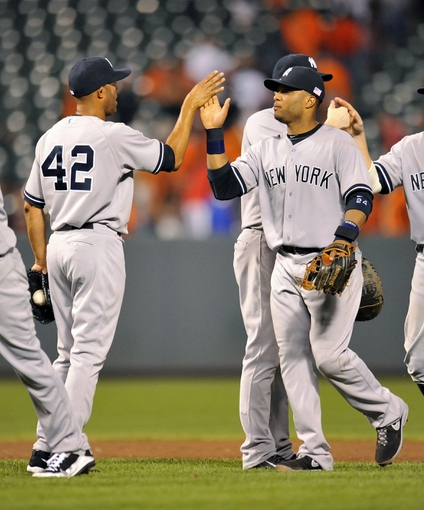 Sep 11, 2013; Baltimore, MD, USA; New York Yankees teammates Mariano Rivera (left) and Robinson Cano (right) celebrate after a game against the Baltimore Orioles at Oriole Park at Camden Yards. The Yankees defeated the Orioles 5-4. Mandatory Credit: Joy R. Absalon-USA TODAY Sports