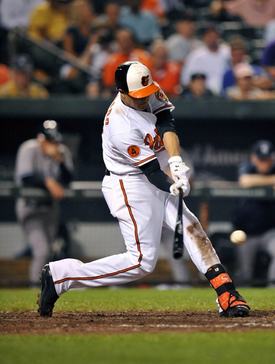 Sep 11, 2013; Baltimore, MD, USA; Baltimore Orioles third baseman Manny Machado (13) singles in the eighth inning against the New York Yankees at Oriole Park at Camden Yards. The Yankees defeated the Orioles 5-4. Mandatory Credit: Joy R. Absalon-USA TODAY Sports