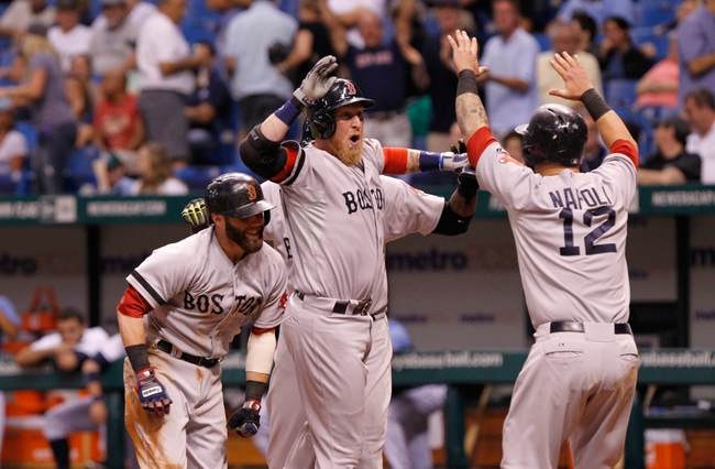 Sep 11, 2013; St. Petersburg, FL, USA; Boston Red Sox left fielder Mike Carp (37) is congratulated by second baseman Dustin Pedroia (15), designated hitter David Ortiz (34) and first baseman Mike Napoli (12) after hitting the go-ahead grand slam during the tenth inning against the Tampa Bay Rays at Tropicana Field. Boston Red Sox defeated the Tampa Bay Rays 7-3. Mandatory Credit: Kim Klement-USA TODAY Sports
