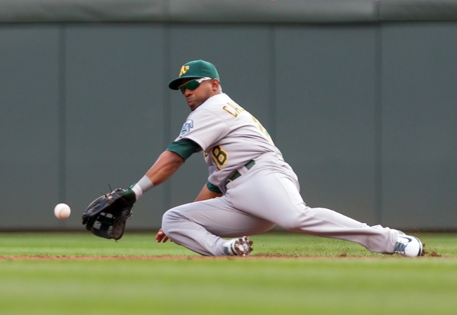Sep 12, 2013; Minneapolis, MN, USA; Oakland Athletics second baseman Alberto Callaspo (18) slides and fields a ground ball in the third inning against the Minnesota Twins at Target Field. Mandatory Credit: Brad Rempel-USA TODAY Sports