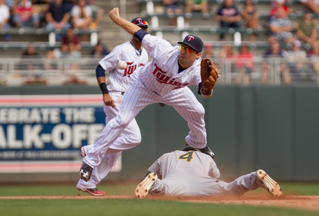 Sep 12, 2013; Minneapolis, MN, USA; Minnesota Twins second baseman Brian Dozier (2) tries to apply the tag as Oakland Athletics center fielder Coco Crisp (4)  slides safely into second in the fifth inning at Target Field. Mandatory Credit: Brad Rempel-USA TODAY Sports