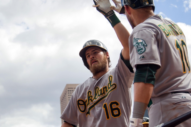 Sep 12, 2013; Minneapolis, MN, USA; Oakland Athletics right fielder Josh Reddick (16) gets congratulated by first baseman Daric Barton (10) after his home run in the eighth inning against the Minnesota Twins at Target Field. Mandatory Credit: Brad Rempel-USA TODAY Sports