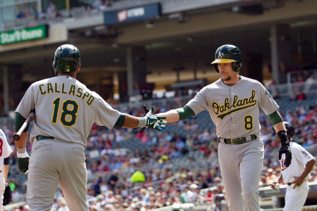 Sep 12, 2013; Minneapolis, MN, USA; Oakland Athletics shortstop Jed Lowrie (8) gets congratulated by infielder Alberto Callaspo (18) in the third inning against the Minnesota Twins at Target Field. Mandatory Credit: Brad Rempel-USA TODAY Sports
