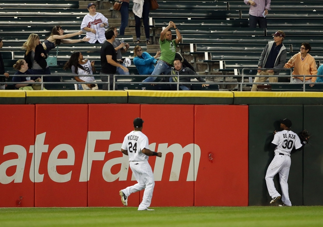 Sep 12, 2013; Chicago, IL, USA; Chicago White Sox outfileders Dayan Viciedo (24) and Alejandro De Aza (30) watch fans try to catch a home run ball hit by Cleveland Indians first baseman Nick Swisher (not pictured) during the first inning at U.S Cellular Field. Mandatory Credit: Jerry Lai-USA TODAY Sports