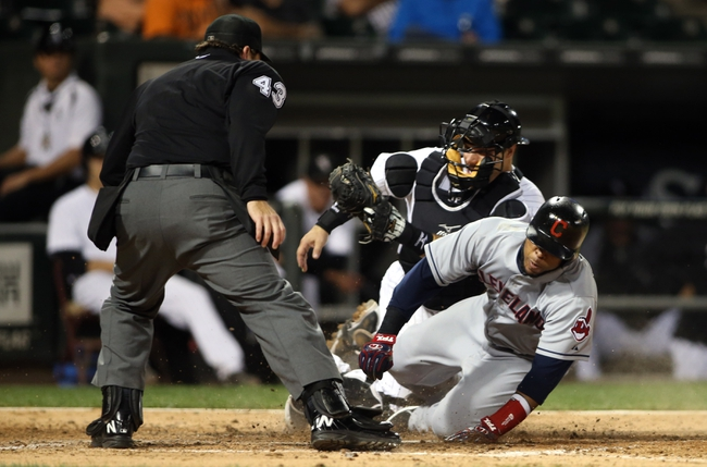 Sep 12, 2013; Chicago, IL, USA; Home plate umpire Paul Schrieber (left) watches as Chicago White Sox catcher Josh Phegley (rear) tags out Cleveland Indians designated hitter Carlos Santana during the fourth inning at U.S Cellular Field. Mandatory Credit: Jerry Lai-USA TODAY Sports