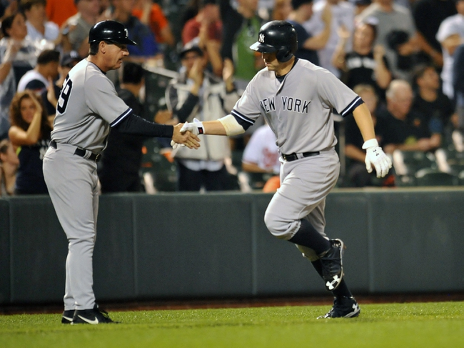 Sep 12, 2013; Baltimore, MD, USA; New York Yankees first baseman Mark Reynolds (39) is congratulated by third base coach Rob Thomson (59) after hitting a two-run home run in the second inning against the Baltimore Orioles at Oriole Park at Camden Yards. Mandatory Credit: Joy R. Absalon-USA TODAY Sports