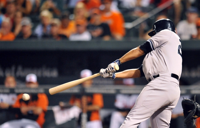 Sep 12, 2013; Baltimore, MD, USA; New York Yankees right fielder Vernon Wells (22) hits a two-run rbi single in the third inning against the Baltimore Orioles at Oriole Park at Camden Yards. Mandatory Credit: Joy R. Absalon-USA TODAY Sports
