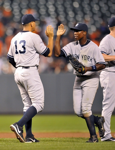 Sep 12, 2013; Baltimore, MD, USA; New York Yankees teammates Alex Rodriguez (13) and Alfonso Soriano (12) celebrate after a game against the Baltimore Orioles at Oriole Park at Camden Yards. The Yankees defeated the Orioles 6-5. Mandatory Credit: Joy R. Absalon-USA TODAY Sports