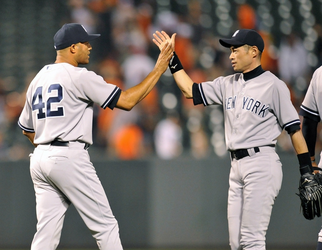 Sep 12, 2013; Baltimore, MD, USA; New York Yankees teammates Mariano Rivera (42) and Ichiro Suzuki (31) celebrate after a game against the Baltimore Orioles at Oriole Park at Camden Yards. The Yankees defeated the Orioles 6-5. Mandatory Credit: Joy R. Absalon-USA TODAY Sports