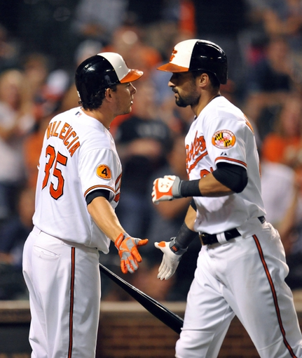 Sep 12, 2013; Baltimore, MD, USA; Baltimore Orioles right fielder Nick Markakis (21) is congratulated by Danny Valencia (35) after hitting a solo home run in the seventh inning against the New York Yankees at Oriole Park at Camden Yards. The Yankees defeated the Orioles 6-5. Mandatory Credit: Joy R. Absalon-USA TODAY Sports