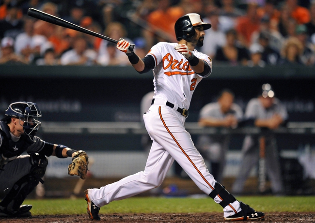 Sep 12, 2013; Baltimore, MD, USA; Baltimore Orioles right fielder Nick Markakis (21) hits a solo home run in the seventh inning against the New York Yankees at Oriole Park at Camden Yards. The Yankees defeated the Orioles 6-5. Mandatory Credit: Joy R. Absalon-USA TODAY Sports