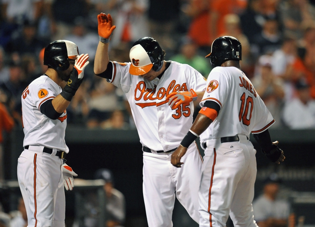 Sep 12, 2013; Baltimore, MD, USA; Baltimore Orioles designated hitter Danny Valencia (35) is congratulated by Nick Markakis (21) and Adam Jones (10) after hitting a three-run home run to tie the game in the eighth inning against the New York Yankees at Oriole Park at Camden Yards. The Yankees defeated the Orioles 6-5. Mandatory Credit: Joy R. Absalon-USA TODAY Sports