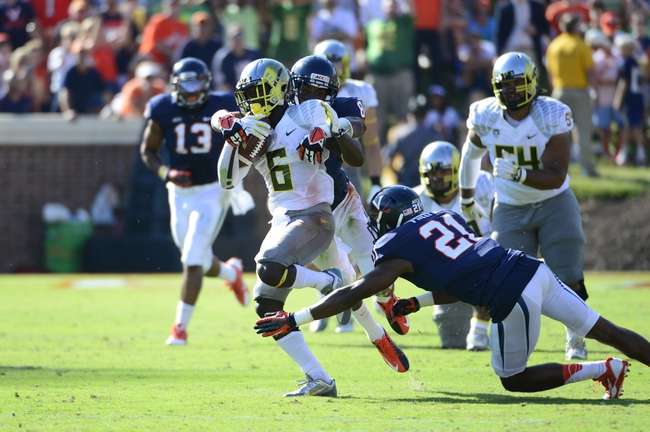 Sep 7, 2013; Charlottesville, VA, USA; Oregon Ducks running back De'Anthony Thomas (6) with the ball as Virginia Cavaliers safeties Anthony Harris (8) and Brandon Phelps (21) defend at Scott Stadium. Mandatory Credit: Bob Donnan-USA TODAY Sports