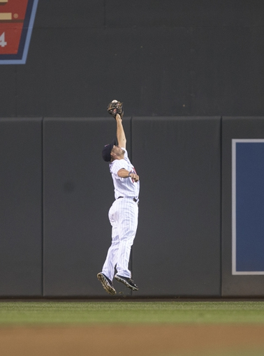 Sep 13, 2013; Minneapolis, MN, USA; Minnesota Twins center fielder Clete Thomas (11) jumps and attempts to catch a fly ball in the second inning against the Tampa Bay Rays at Target Field. Mandatory Credit: Jesse Johnson-USA TODAY Sports