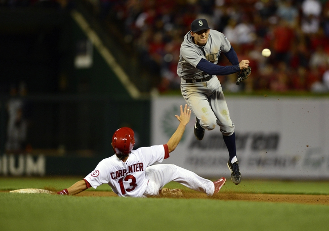 Sep 13, 2013; St. Louis, MO, USA; Seattle Mariners shortstop Brad Miller (top) leaps over St. Louis Cardinals second baseman Matt Carpenter (13) but is unable to complete the double play allowing pinch runner Pete Kozma (not pictured) to score and tie the game during the eighth inning at Busch Stadium. St. Louis defeated Seattle 2-1 in 10 innings. Mandatory Credit: Jeff Curry-USA TODAY Sports