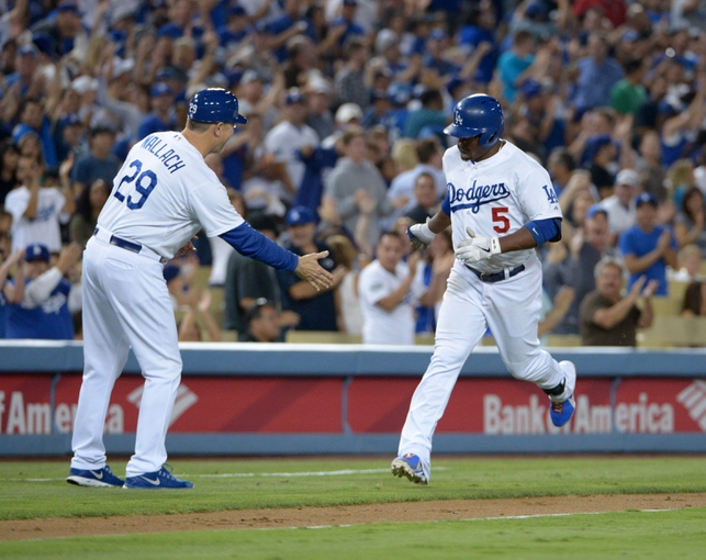 Sep 13, 2013; Los Angeles, CA, USA; Los Angeles Dodgers third baseman Juan Uribe (5) is congratulated by third base coach Tim Wallach (29) after hitting a two-run home run in the sixth inning against the San Francisco Giants at Dodger Stadium. Mandatory Credit: Kirby Lee-USA TODAY Sports