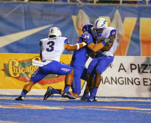 Sep 13, 2013; Boise, ID, USA; Air Force Falcons defensive back Christian Spears (21) picks off a pass from Boise State Broncos quarterback Joe Southwick (not pictured) and is tackled by wide receiver Kirby Moore (34) during the second half at Bronco Stadium. Boise State defeated the Air Force 42-20. Mandatory Credit: Brian Losness-USA TODAY Sports