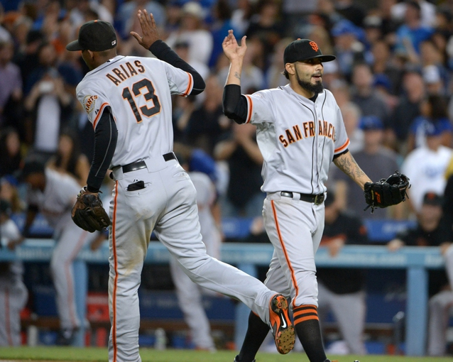 Sep 13, 2013; Los Angeles, CA, USA; San Francisco Giants reliever Sergio Romo (54, right) celebrates with shortstop Joaquin Arias (13) at the end of the game against the Los Angeles Dodgers at Dodger Stadium. The Giants defeated the Dodgers 4-2. Mandatory Credit: Kirby Lee-USA TODAY Sports