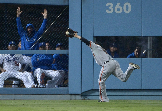 Sep 13, 2013; Los Angeles, CA, USA; San Francisco Giants left fielder Juan Perez (2) catches a fly ball by Los Angeles Dodgers left fielder Scott Van Slyke (not pictured) in the sixth inning as Dodgers pitcher Brian Wilson (second from left) reacts at Dodger Stadium. The Giants defeated the Dodgers 4-2. Mandatory Credit: Kirby Lee-USA TODAY Sports