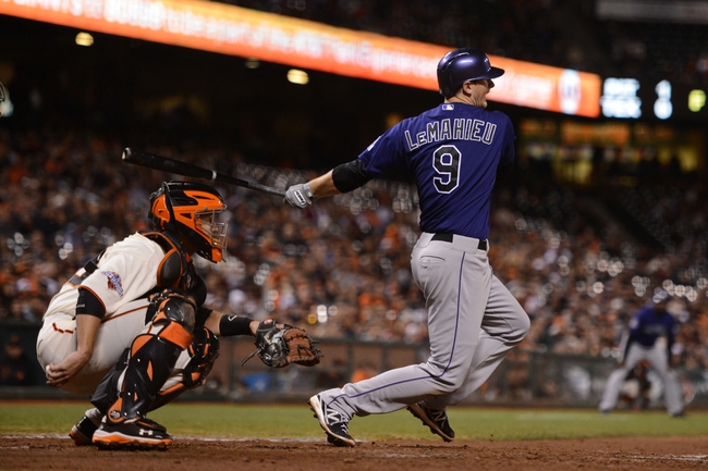 September 9, 2013; San Francisco, CA, USA; Colorado Rockies second baseman D.J. LeMahieu (9) bats in front of San Francisco Giants catcher Buster Posey (28, left) during the 10th inning at AT&T Park. The Giants defeated the Rockies 3-2 in 10 innings. Mandatory Credit: Kyle Terada-USA TODAY Sports