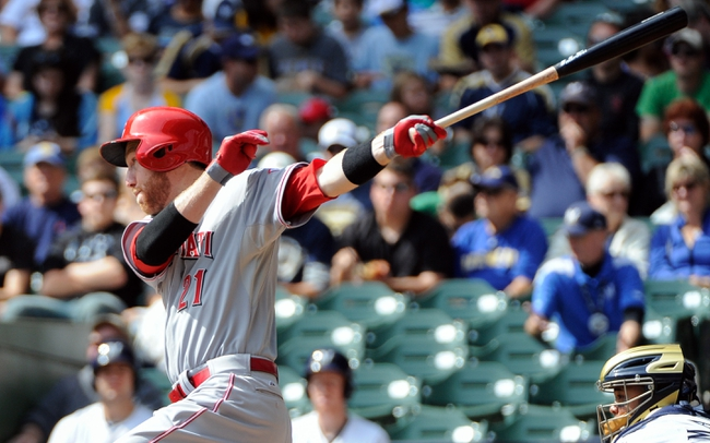 Sep 14, 2013; Milwaukee, WI, USA; Cincinnati Reds third baseman Todd Frazier hits a single to drive in a run in the first inning against the Milwaukee Brewers at Miller Park. Mandatory Credit: Benny Sieu-USA TODAY Sports