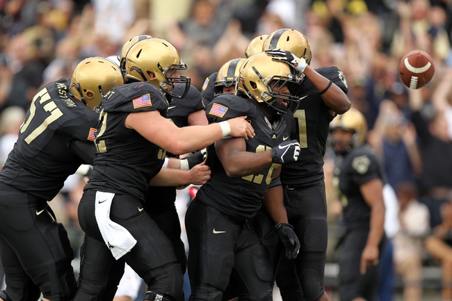 Sep 14, 2013; West Point, NY, USA; Army Black Knights running back Larry Dixon (26) flips the ball and celebrates with teammates after scoring a touchdown against the Stanford Cardinal during the first half at Michie Stadium. Mandatory Credit: Danny Wild-USA TODAY Sports