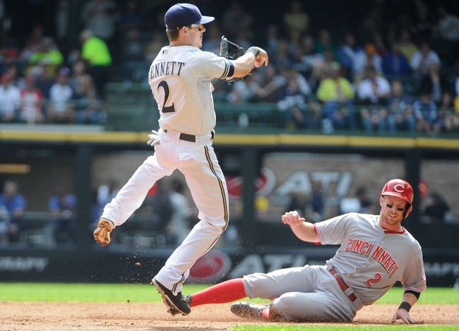 Sep 14, 2013; Milwaukee, WI, USA; Milwaukee Brewers second baseman Scooter Gennett (left) completes a double play after forcing out Cincinnati Reds shortstop Zack Cozart in the 3rd inning at Miller Park. Mandatory Credit: Benny Sieu-USA TODAY Sports