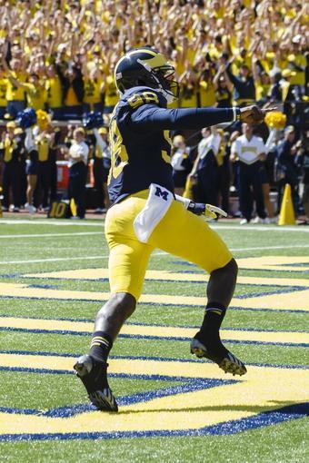 Sep 14, 2013; Ann Arbor, MI, USA; Michigan Wolverines quarterback Devin Gardner (98) celebrates touch down in the third quarter against the Akron Zips at Michigan Stadium. Mandatory Credit: Rick Osentoski-USA TODAY Sports