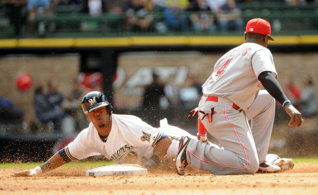 Sep 14, 2013; Milwaukee, WI, USA;  Milwaukee Brewers shortstop Jean Segura (left) steals 2nd base before Cincinnati Reds second baseman Brandon Phillips can apply the tag in the fifth inning at Miller Park. Mandatory Credit: Benny Sieu-USA TODAY Sports