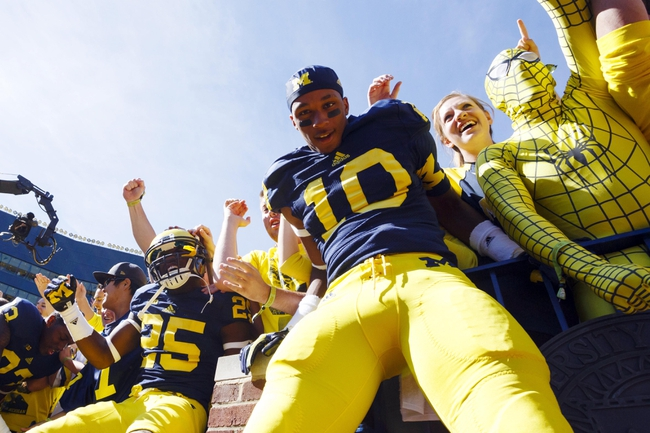 Sep 14, 2013; Ann Arbor, MI, USA; Michigan Wolverines defensive back Dymonte Thomas (25) and wide receiver DaMario Jones (10) celebrate with fans after the game against the Akron Zips at Michigan Stadium. Mandatory Credit: Rick Osentoski-USA TODAY Sports
