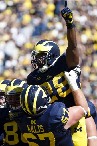 Sep 14, 2013; Ann Arbor, MI, USA; Michigan Wolverines running back Fitzgerald Toussaint (28) is lifted into the air by offensive linesman Kyle Kalis (67) after he scores a touchdown in the fourth quarter against the Akron Zips at Michigan Stadium. Michigan won 28-24. Mandatory Credit: Rick Osentoski-USA TODAY Sports