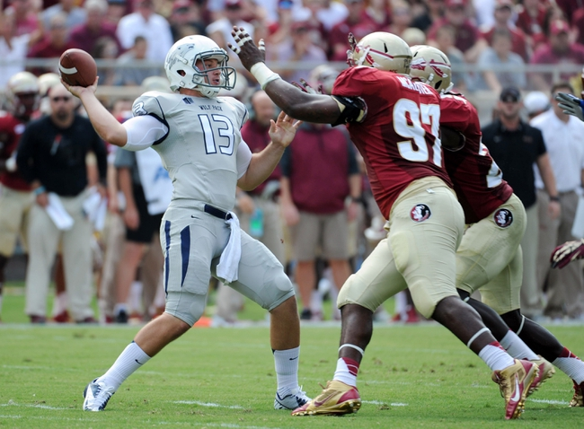 Sep 14, 2013; Tallahassee, FL, USA; Nevada Wolf Pack quarterback Devin Combs (13) throws the ball as he is pressured by Florida State Seminoles defensive tackle Demonte McAllister (97) during the first half of the game at Doak Campbell Stadium. Mandatory Credit: Melina Vastola-USA TODAY Sports