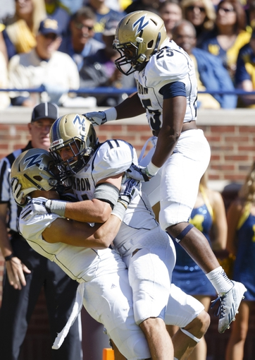 Sep 14, 2013; Ann Arbor, MI, USA; Akron Zips wide receiver L.T. Smith (3) wide receiver Zach D'Orazio (11) running back D.J. Jones (25) celebrate an apparent touchdown in the fourth quarter against the Michigan Wolverines at Michigan Stadium. The play was overturned on replay with the ball placed on the one yard line. Michigan won 28-24. Mandatory Credit: Rick Osentoski-USA TODAY Sports