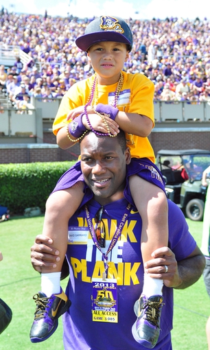 Sep 14, 2013; Greenville, NC, USA;  East Carolina Pirates former quarterback David Garrard (bottom) and his son watch the Pirates play against the Virginia Tech Hokies at Dowdy-Ficklen Stadium. Mandatory Credit: Rob Kinnan-USA TODAY Sports