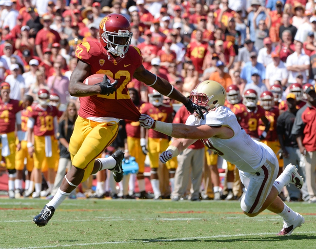 Sep 14, 2013; Los Angeles, CA, USA; USC Trojans running back Justin Davis (22) breaks a tackle by Boston College Eagles defensive back Sean Sylvia (19) on his way to a second half touchdown at Los Angeles Memorial Coliseum. 